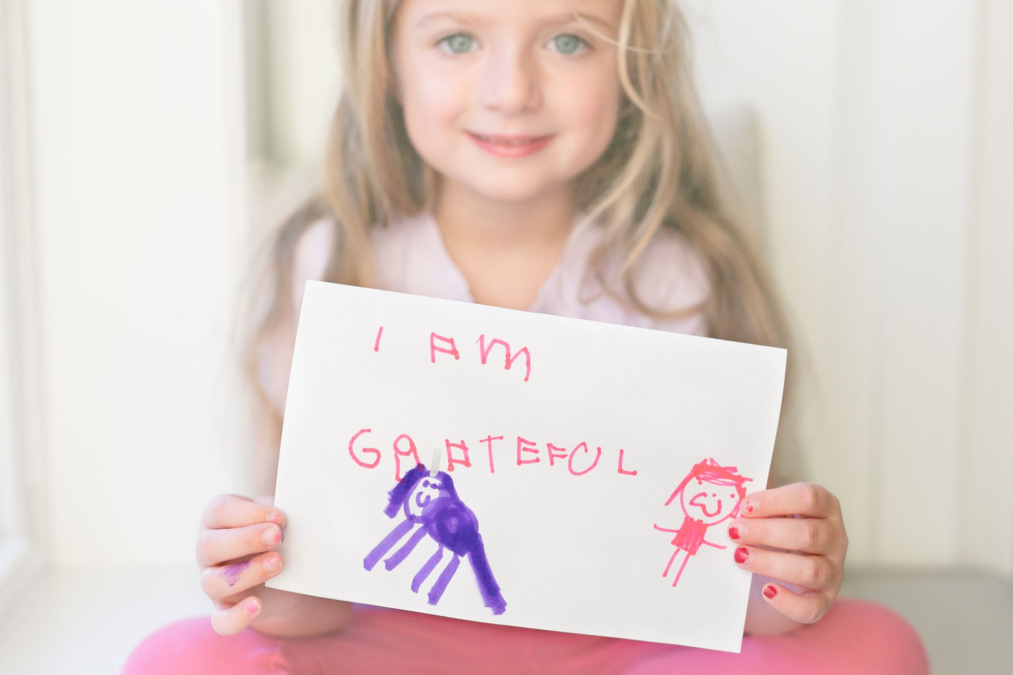 """A young girl with blond hair and big blue eyes, the author's daughter, is holding up a hand-made thank you card with the words """"I AM GRATEFUL"""" written in pink marker above a drawing of a purple unicorn and a smiling person."""